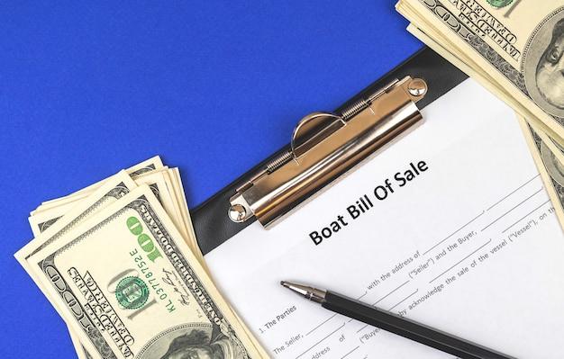 Kup nową łódź z oficjalnymi dokumentami. łódź rachunek umowy sprzedaży na niebieski stół biurowy z pieniędzmi i piórem. zdjęcie w widoku z góry