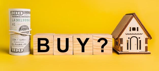 Kup z domowym miniaturowym modelem i pieniędzmi na żółtym tle. pojęcie biznesu, finansów, kredytu, podatków, nieruchomości, domu, mieszkania