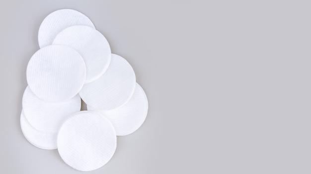 Kupa białych miękkich płatków kosmetycznych lub krążków na szarym stole z miejscem na kopię