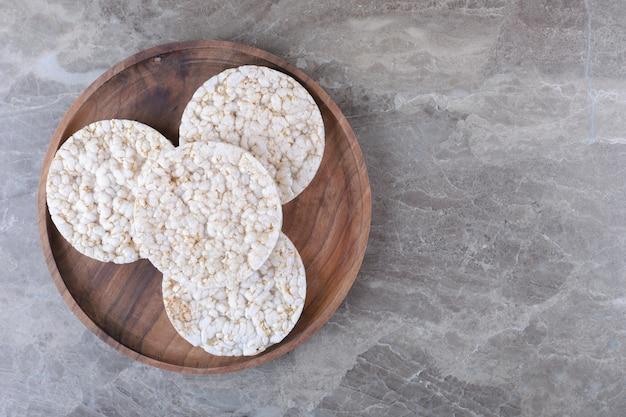 Kupa dmuchanych wafli ryżowych na drewnianej tacy na marmurowej powierzchni