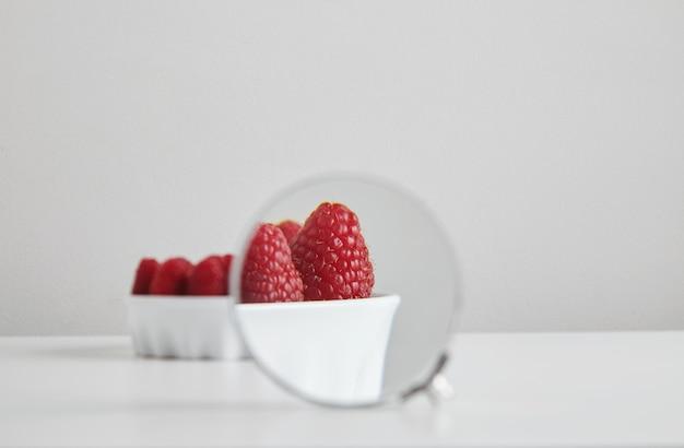 Kupa dojrzałego organicznego pożywienia malinowego w koncepcji ceramicznej miski dla zdrowego odżywiania i odżywiania na białym stole, magnetyzowana przez lupę lornetkową, aby zobaczyć szczegóły