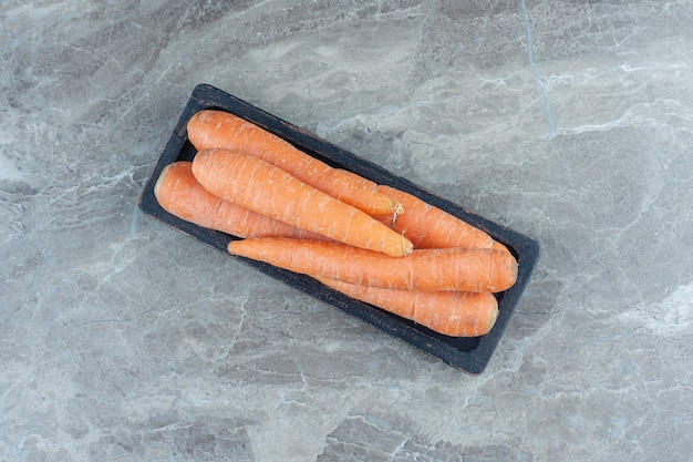 Kupa marchewek na marmurowym stole.