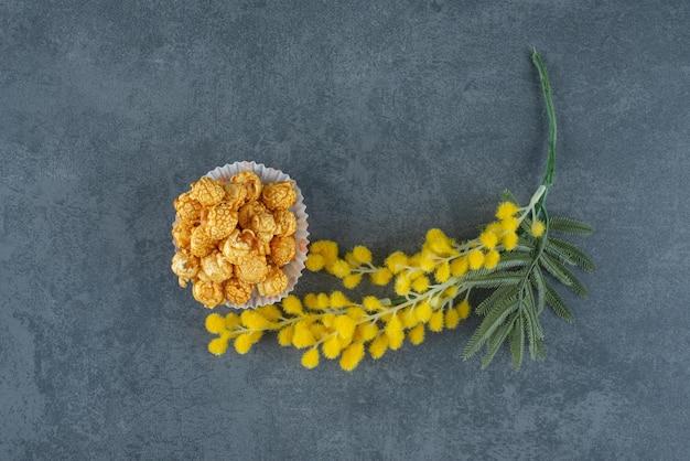 Kupa popcornu w karmelu obok łodygi wrażliwej rośliny na marmurze