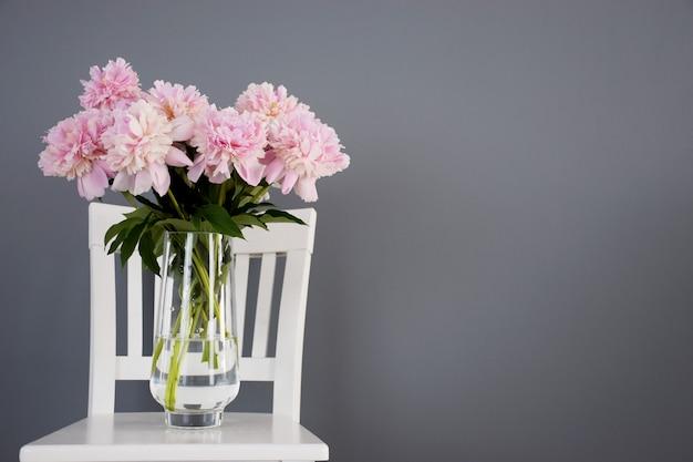 Kupa różowe piwonie w rozkwicie w szklanym wazonie na białym krześle na tle szarej ściany