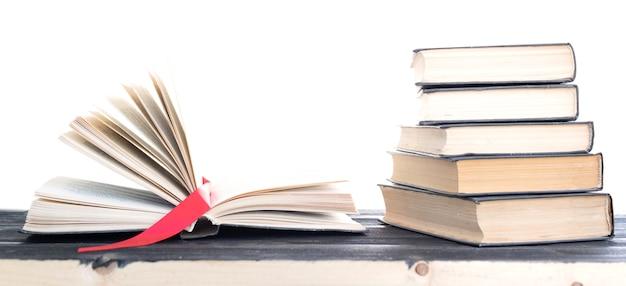 Kupa rzadkich książek. otwarta książka, twarda książka na drewnianym stole.