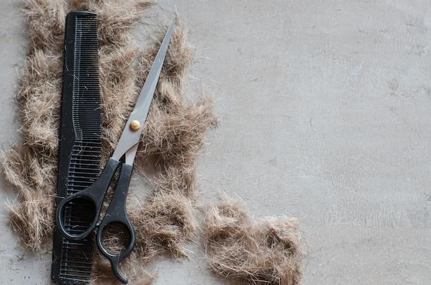 Kupa ściętych włosów, nożyczki do strzyżenia i grzebienia. narzędzia do strzyżenia.
