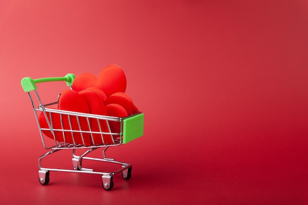 Kupa serc w mini wózku spożywczym, na czerwonej ścianie, koncepcja sprzedaży i miłości, walentynki, miejsce na kopię, poziome, widok z boku