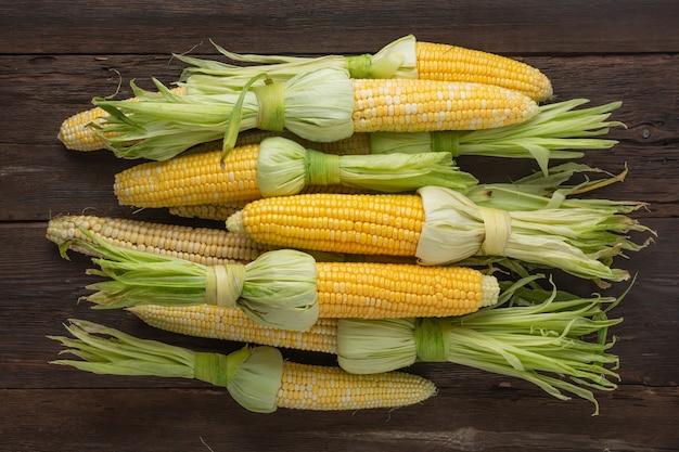 Kupa świeżej surowej kukurydzy w kolbie na drewnianym stole, widok z góry