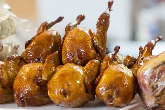 Kupa wędzonych korpusów kurczaków na rynku