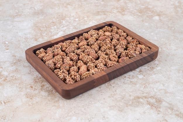 Kupie brązowe cukierki orzechowe umieszczone na drewnianej tablicy.