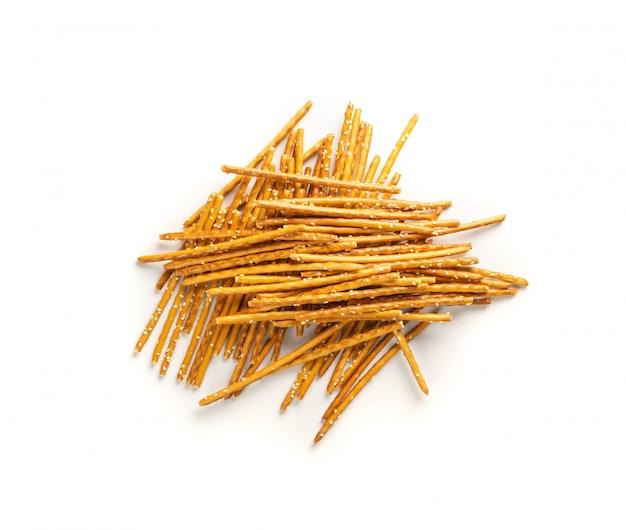 Kupie chrupiące laski soli z białym sezamem na białym tle. słone paluszki, grissini lub cienkie paluszki chlebowe widok z góry