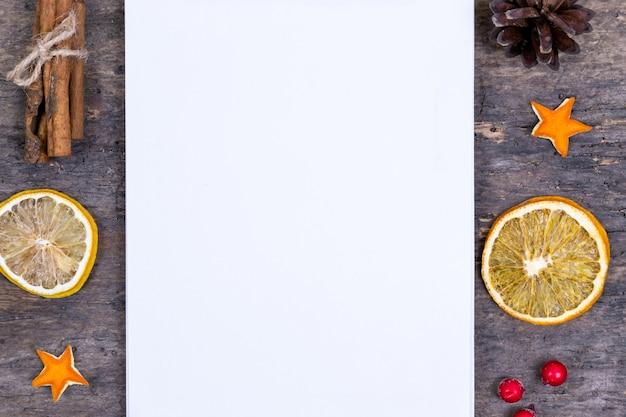 Kupie cynamonu, suszonych pomarańczy i mandarynek na starym drewnianym stole z białym pustym kawałkiem papieru. świąteczne ozdoby. kartka świąteczna