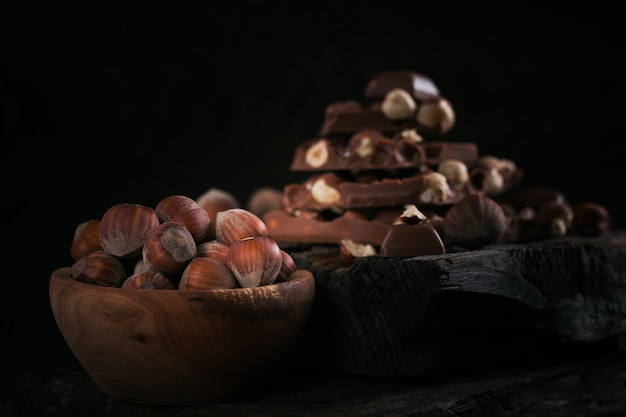 Kupie czekoladę mleczną z orzechów laskowych i orzechy na ciemnej powierzchni drewnianych