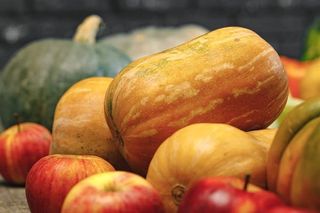 Kupie czerwone jabłka i duże banie na powierzchni drewnianych