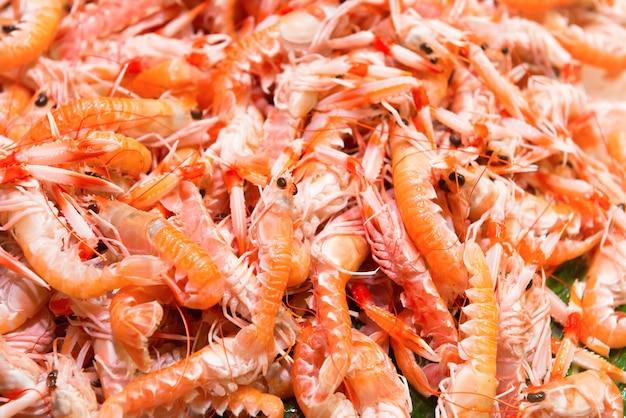 Kupie czerwone świeże krewetki na rynku. tekstura owoców morza na tle