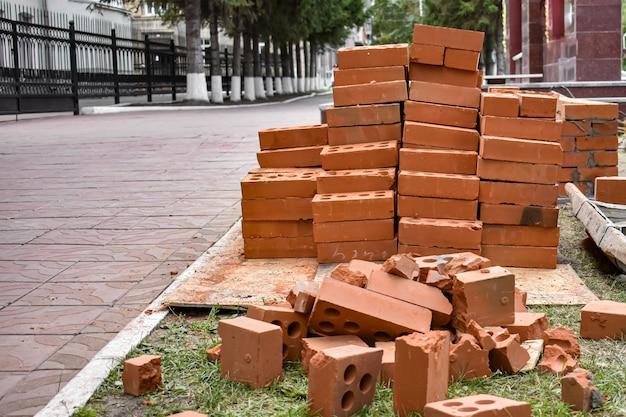 Kupie czerwonych cegieł na budowie w mieście. przemysłowe części murowane, sprzęt budowlany