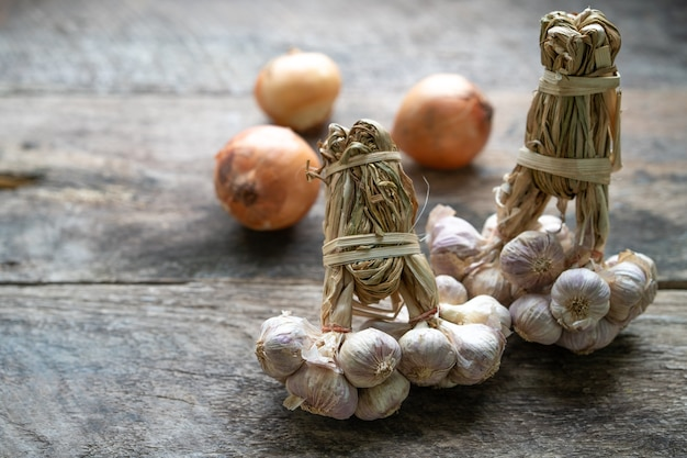 Kupie dojrzałego czosnku i cebuli na drewnianym stole