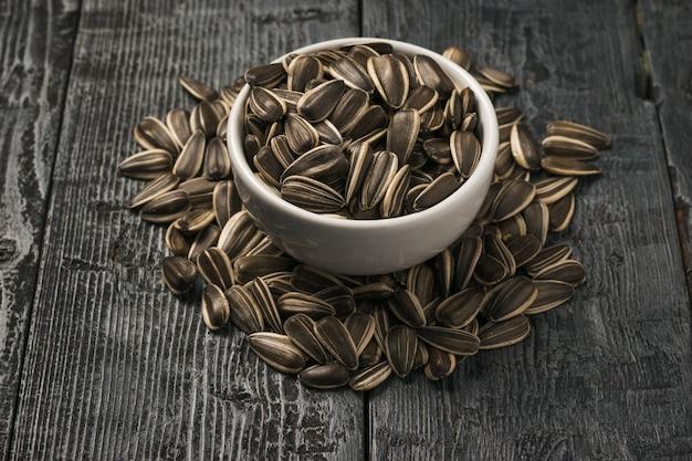 Kupie dużych nasion słonecznika i białej porcelanowej miski na drewnianym stole.