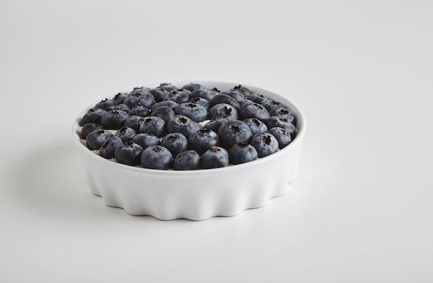 Kupie ekologiczne pożywienie przeciwutleniające borówki w koncepcji ceramicznej miski dla zdrowego odżywiania i odżywiania na białym stole