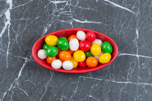 Kupie kolorowe cukierki w czerwonej misce.
