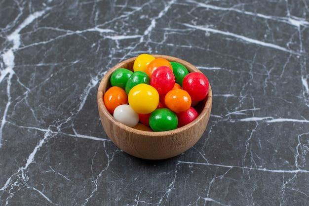 Kupie kolorowe cukierki w drewnianej misce.