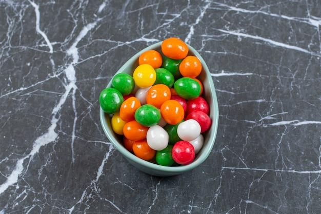Kupie kolorowe cukierki w niebieskiej misce.