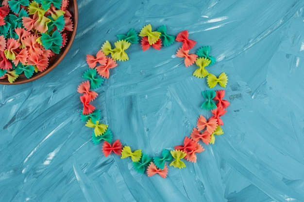 Kupie kolorowe surowe makarony farfalle na niebieskim tle.