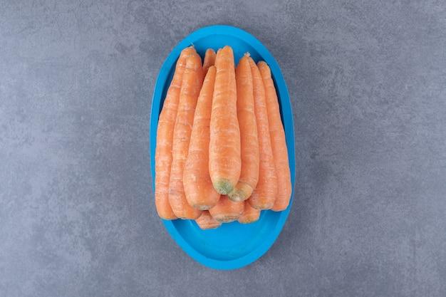 Kupie marchewki na niebieskiej tacy, na marmurowej powierzchni.