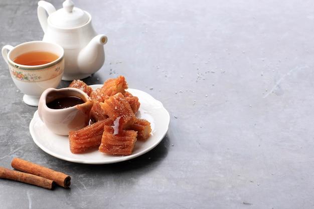 Kupie mini churros lub churro z dżemem w sosie czekoladowym, podawane z herbatą. ścieśniać. kopiuj miejsce na tekst