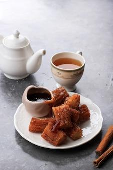 Kupie mini churros lub churro z dżemem w sosie czekoladowym, podawane z herbatą. ścieśniać