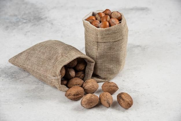 Kupie organicznych orzechów laskowych i orzechów włoskich w płótnie na marmurowym stole.