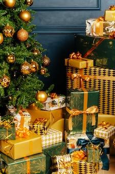 Kupie owinięte zielone i złote prezenty na boże narodzenie