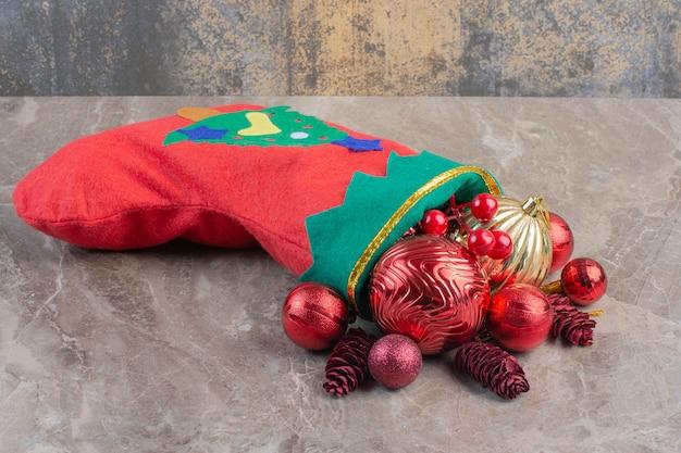Kupie ozdoby choinkowe i skarpety świąteczne na marmurze.