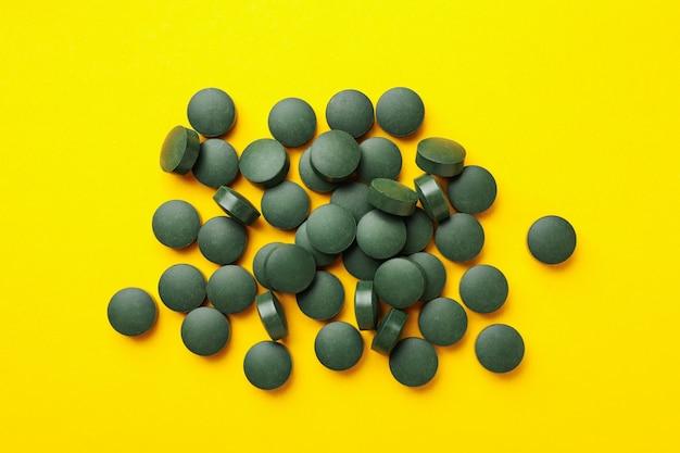 Kupie pigułki spiruliny na żółtym tle, widok z góry