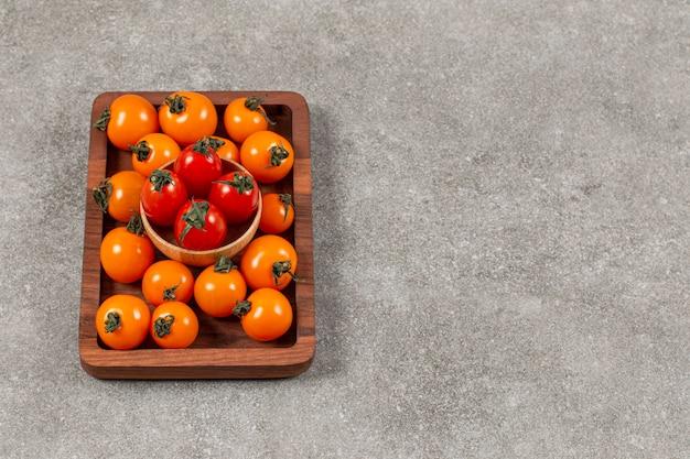 Kupie pomidory czereśniowe na drewnianej tablicy.
