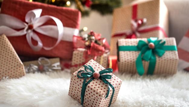 Kupie prezentów świątecznych nad jasną ścianą na drewnianym stole z wygodnym dywanikiem. ozdoby świąteczne