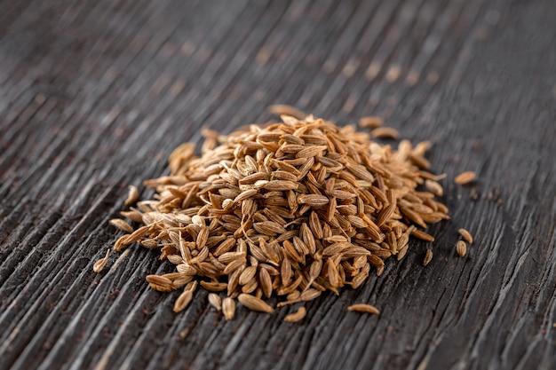 Kupie przyprawione nasiona kminku przyprawy na ciemnym drewnianym stole, poziome