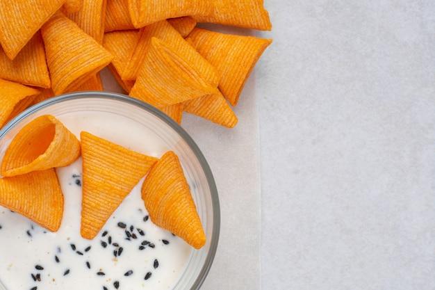 Kupie pyszne chipsy w kształcie trójkąta i jogurt na kamieniu.