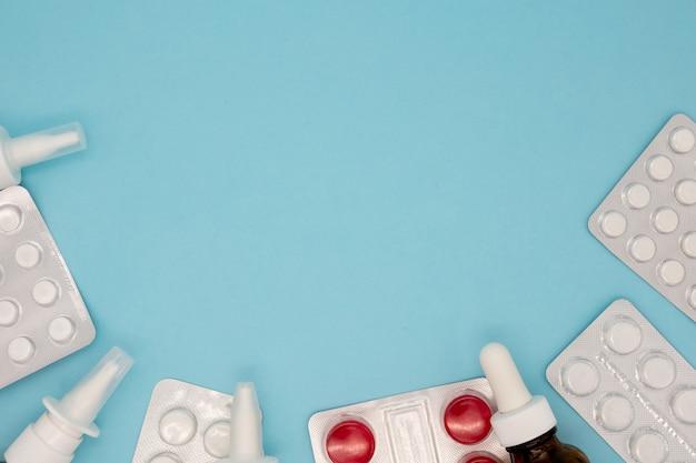 Kupie rozproszone kapsułki na niebieskim tle. kapsułki izolowane biała kapsułka apteka butelka pigułka pojęcie narkotyków