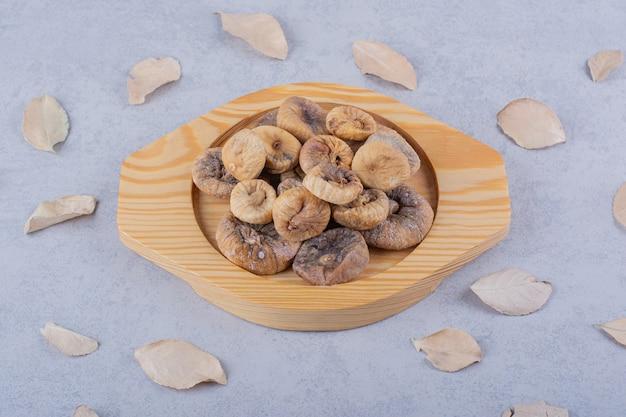 Kupie słodkich suszonych fig umieszczonych na drewnianym talerzu z liśćmi.