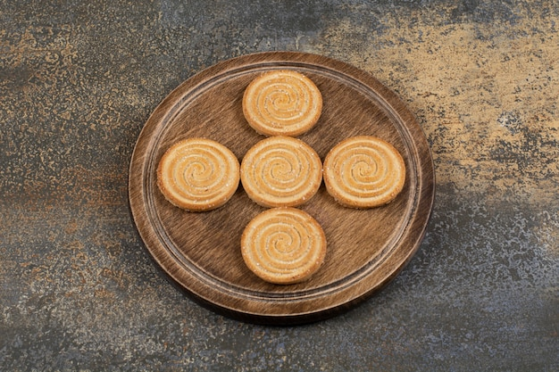 Kupie smaczne ciastka na drewnianym talerzu.