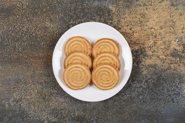 Kupie smaczne ciastka okrągłe na białym talerzu.
