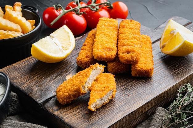 Kupie smażone na złoto paluszki rybne z zestawem sosu z białego czosnku, na drewnianej desce do krojenia, na czarnym tle