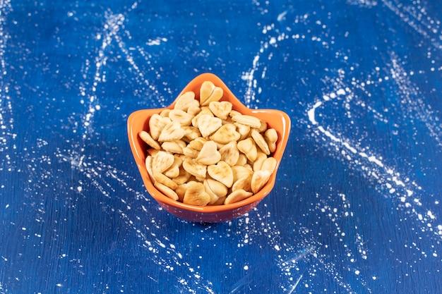 Kupie solone krakersy w kształcie serca umieszczone w pomarańczowej misce.
