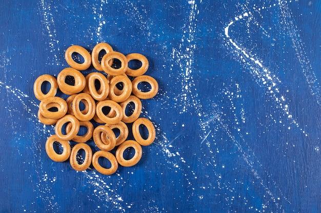 Kupie solone okrągłe precle umieszczone na marmurowym stole.