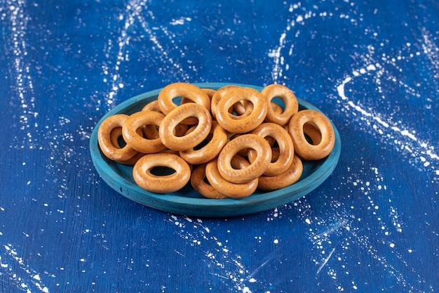 Kupie solonych okrągłych precli umieszczonych na niebieskim talerzu