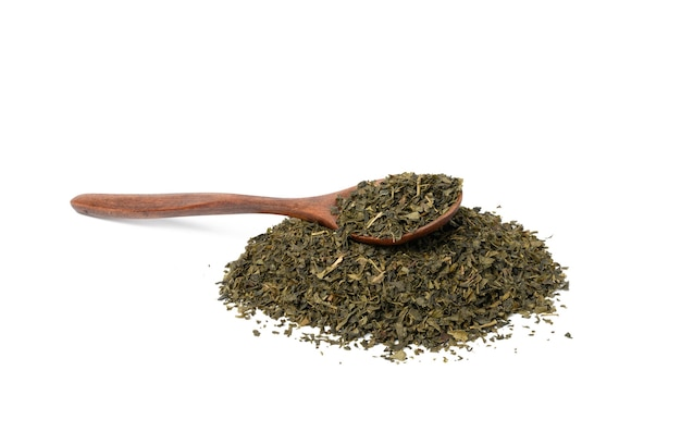Kupie suchą zieloną herbatę i brązowy drewnianą łyżką na białym tle