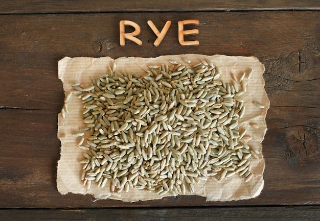 Kupie suche ziarno żyta surowego z widokiem z góry drewniane litery