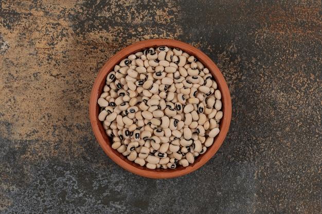Kupie surowej białej fasoli w ceramicznej misce.