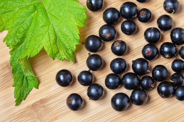 Kupie świeże dojrzałe czarne porzeczki na drewnianym stole z liściem